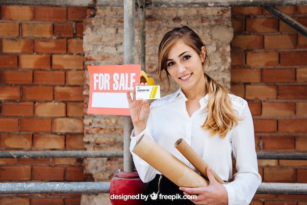 Businesswoman showing business card in front of construction site