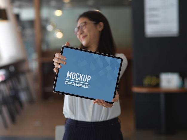 Деловая женщина показывает макет планшета с пустым экраном, стоя в офисной комнате, отсечения путь