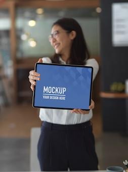 事務室に立っている間、空白の画面のタブレット、クリッピングパスをモックアップを示す実業家