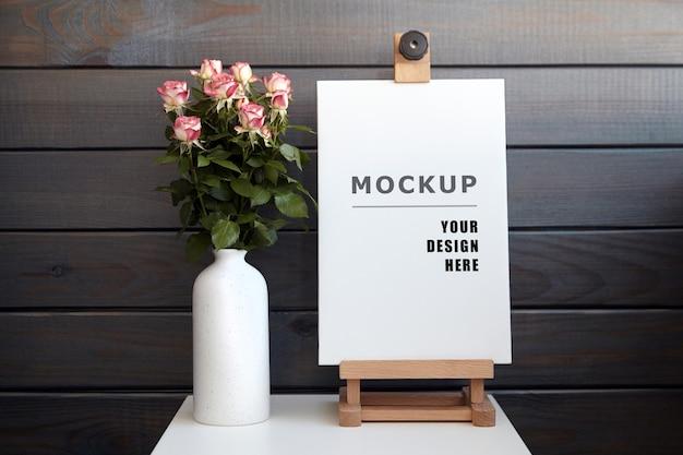 Макет холста на белом столе с вазой цветов