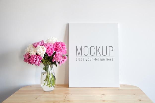 白い壁の背景に木製のテーブルにピンクの花とキャンバスのモックアップ