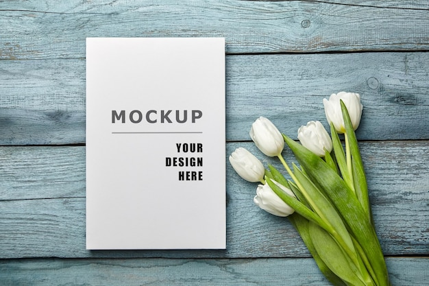 Canvas print mockup and white tulip flowers on blue wooden surface flat lay