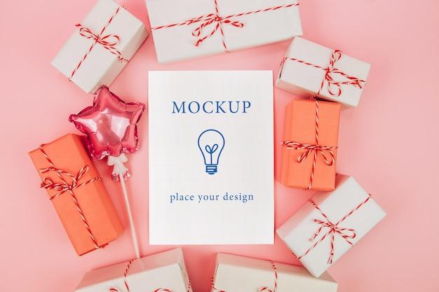 Открытка и коробки с подарками на розовом фоне, макет