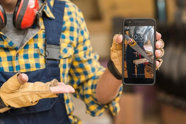 Carpenter che tiene smartphone mockup