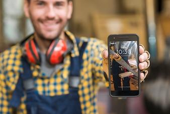 Carpenter holding smartphone mockup