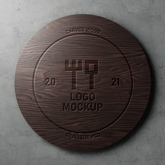 Резной гравированный реалистичный макет логотипа на полированном круге темного дерева на бетонной стене
