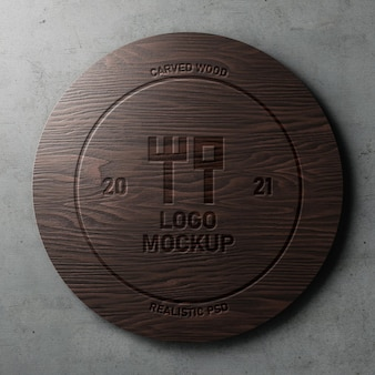 Carved engraved realistic logo mockup on polished circle dark wood on concrete wall