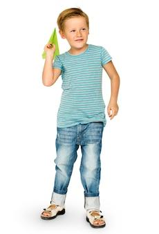 Кавказский этнический мальчик запускает бумажную плоскость