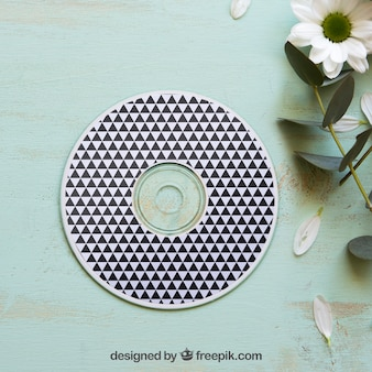 Cd mockup next to flower