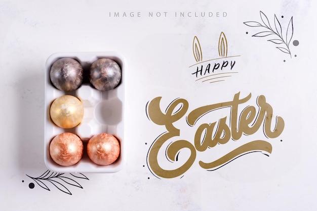 Керамический поднос для яиц с расписанными золотом и серебром пасхальными яйцами на белой каменной поверхности макета