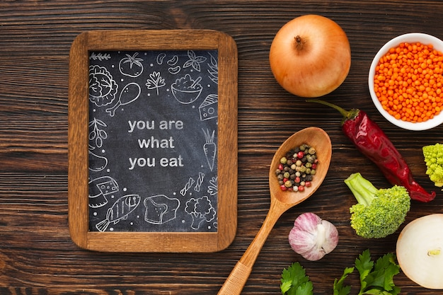 Chalkboard with organic vegetables beside