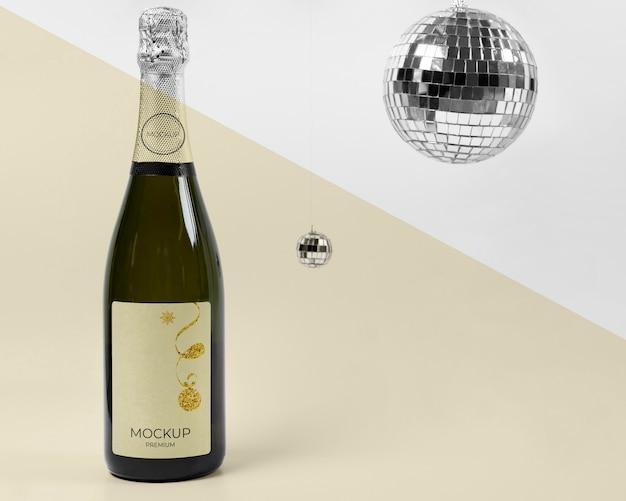 Mock-up di bottiglia di champagne e palle da discoteca