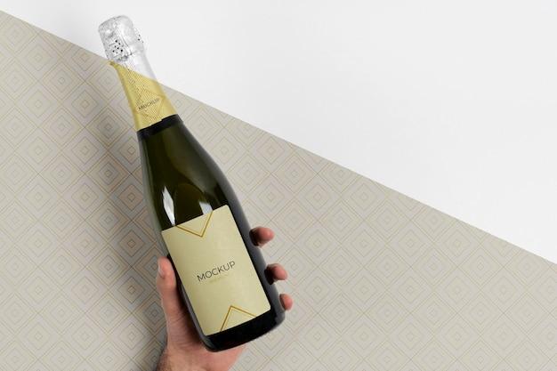 Mock-up di bottiglia di champagne tenuto in mano