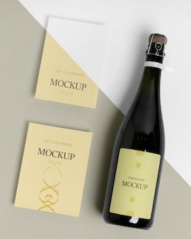 Mock-up di bottiglia di champagne e biglietti d'invito