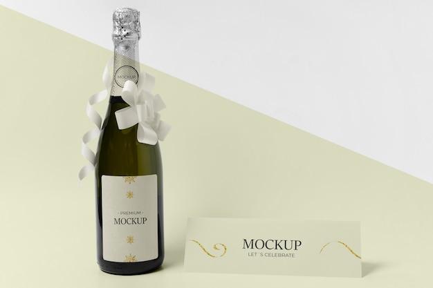 Mock-up di bottiglia di champagne con nastri e fiocchi bianchi