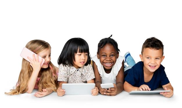 Cheerful children holding digital devices