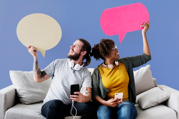 Cheerful couple holding speech bubble icons