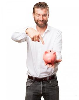 Cheerful man pointing at his piggy bank