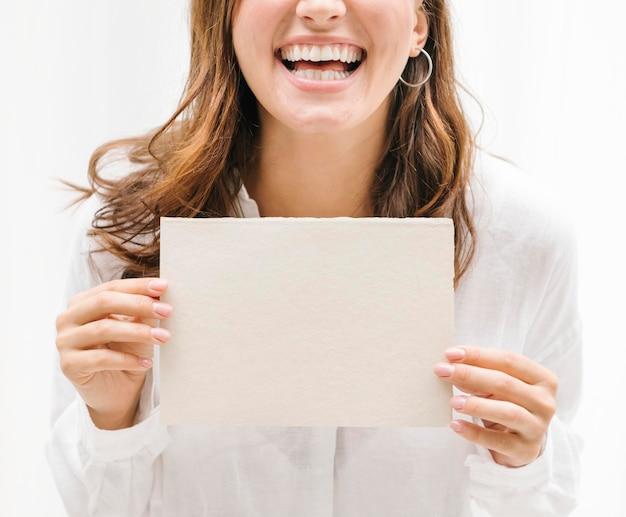 ベージュのカードのモックアップを示す陽気な女性