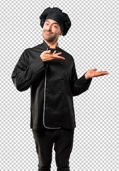 Chef man in black uniform extending hands to the side and smiling for presenting