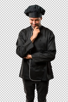 Chef man in black uniform standing and looking down with the hand on the chin