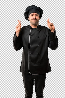Chef man in black uniform with fingers crossing and wishing the best. making a wish.