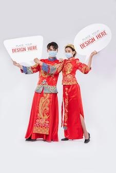 中国人男性と中国人女性が空白の吹き出しモックアップを保持します