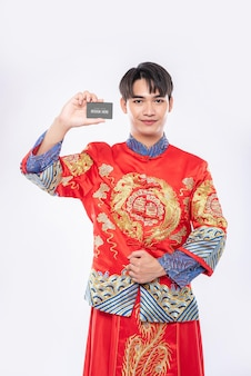 中国人男性は空白のクレジットカードのモックアップを保持します