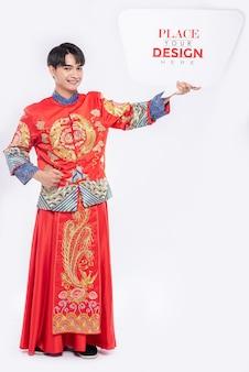 中国人男性が空白の吹き出しモックアップを保持します