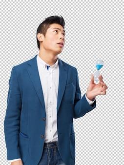 Китайский мужчина держит песочные часы
