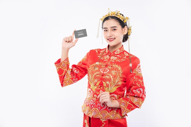 中国の女性は空白のクレジットカードのモックアップを保持します