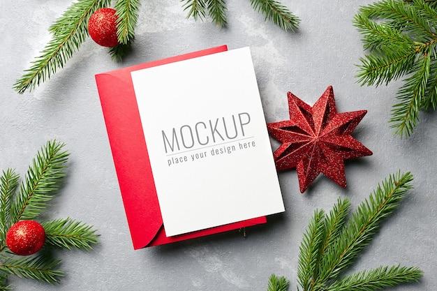 赤い封筒とお祝いの装飾が施されたクリスマスと新年のグリーティングカードのモックアップ
