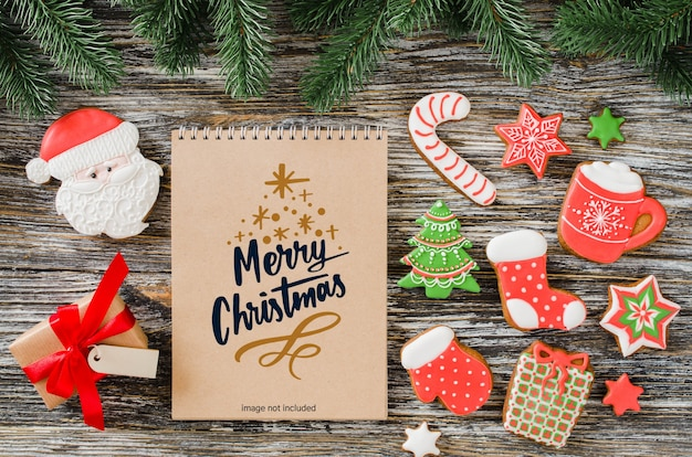 Christmas background with brown notebook mockup, gingerbread cookies and fir tree