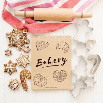 ノートブックのモックアップ、ジンジャーブレッドの台所用品とクリスマスの背景