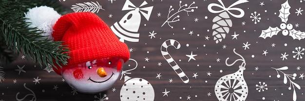 Рождественский баннер со снеговиком и еловыми ветками на темном деревянном фоне.