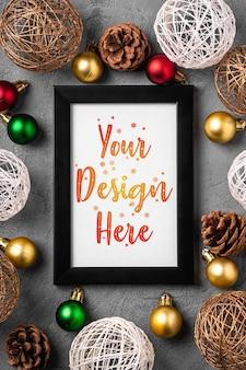 空の額縁のクリスマス作曲。カラフルなつまらないものと松ぼっくりの装飾。モックアップグリーティングカードテンプレート