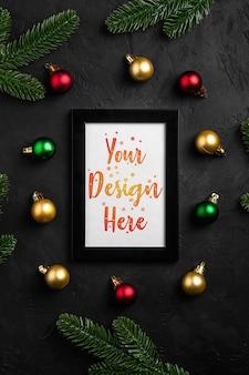 空の額縁のクリスマス作曲。カラフルな飾り、松ぼっくり、モミの針の装飾。グリーティングカードテンプレートのモックアップ