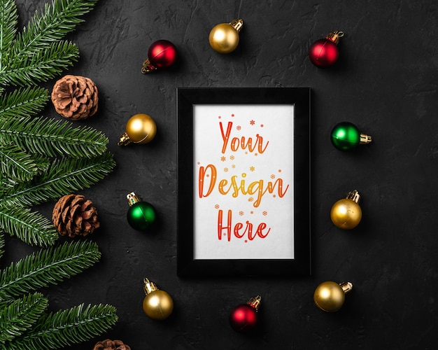 Christmas composition with empty picture frame. colorful ornament, pine cones and fir needles decorations. mock up greetings card template