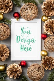 空の額縁のクリスマス作曲。金色の飾り、松ぼっくり、モミの針の装飾。グリーティングカードテンプレートのモックアップ