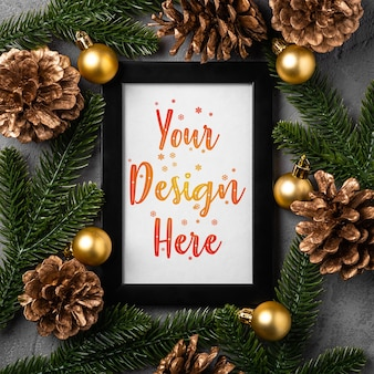 Christmas composition with empty picture frame. golden ornament, pine cones and fir needles decorations. mock up greetings card template