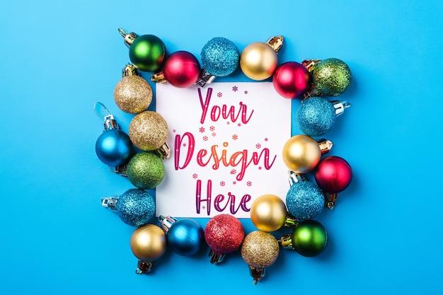 白い四角いコピースペースのクリスマス作曲。カラフルな飾りとつまらない装飾。モックアップグリーティングカードテンプレート
