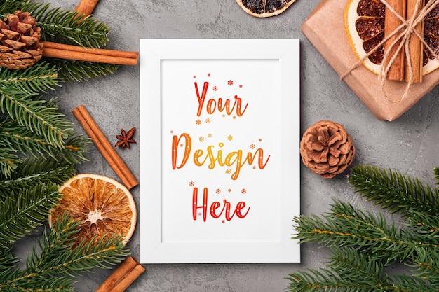 Композиция макета новогодней рамки с подарочной коробкой, корицей, анисом, сухофруктами, шишками и хвоей на сером