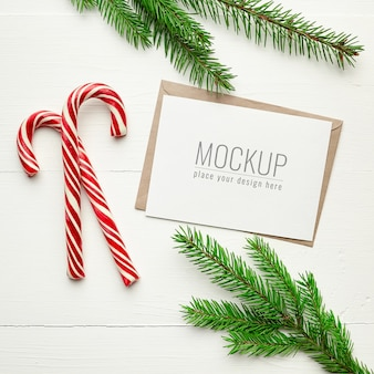 Christmas greeting card mockup with candy canes and fir tree branches