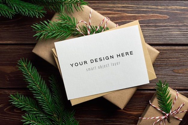 Christmas greeting card mockup with christmas gift boxes and fir tree branches