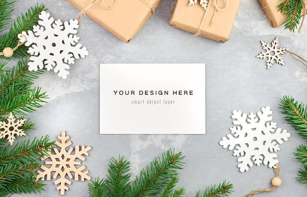 クリスマスツリーの枝と装飾が施されたクリスマスグリーティングカードのモックアップ