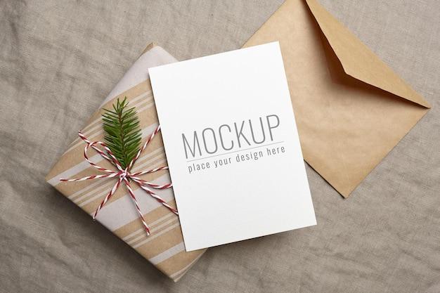 リネンの背景に装飾されたギフトボックスと封筒のクリスマスグリーティングカードのモックアップ