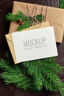 Макет рождественской открытки с украшенной подарочной коробкой и еловыми ветками