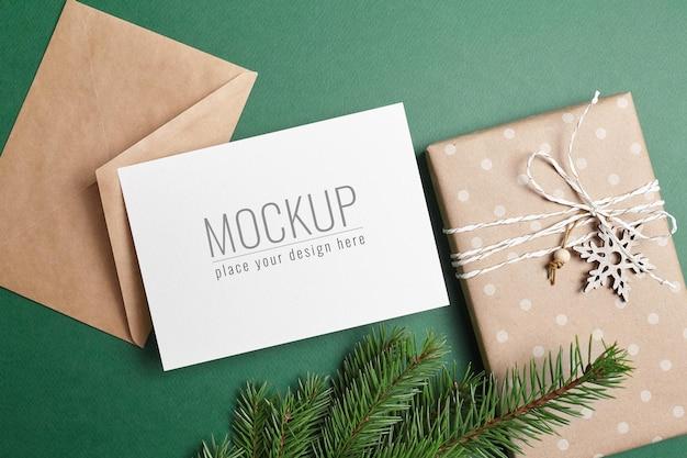 装飾されたギフトボックス、封筒、緑のモミの木の枝とクリスマスグリーティングカードのモックアップ