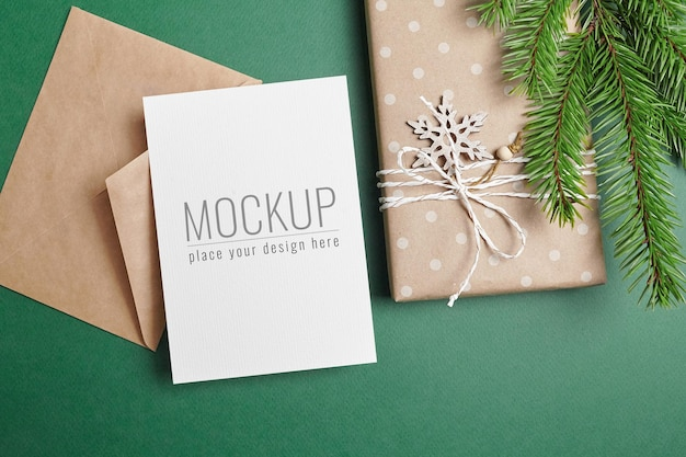 Christmas greeting card mockup with decorated gift box, envelope and green fir tree branch