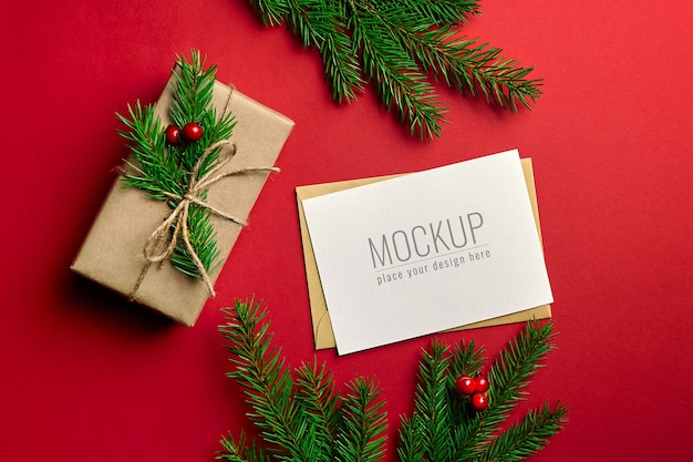 Christmas greeting card mockup with decorated gift box and fir tree branches
